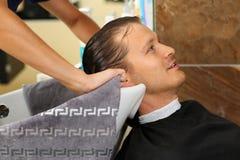 Mani femminili che puliscono capelli dell'uomo sorridente bello con l'asciugamano Immagini Stock