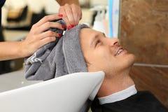 Mani femminili che puliscono capelli dell'uomo sorridente bello con l'asciugamano Fotografia Stock