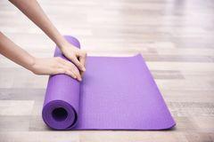 Mani femminili che rotolano la stuoia di yoga sul pavimento Immagini Stock