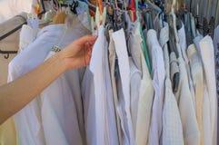 Mani femminili che scelgono i vestiti Immagine Stock Libera da Diritti