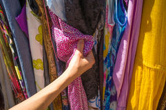 Mani femminili che scelgono i vestiti Fotografie Stock