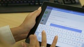 Mani femminili che scrivono sul touchpad sulla tavola stock footage