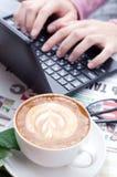Mani femminili che scrivono testo a macchina su una tastiera del netbook fotografia stock