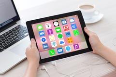 Mani femminili che tengono compressa con i apps delle icone dello schermo domestico Immagini Stock