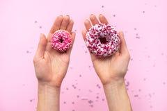 Mani femminili che tengono due guarnizioni di gomma piuma Fondo rosa fotografia stock