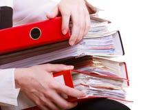 Mani femminili che tengono i documenti delle cartelle della pila. Donna sovraccarica di affari. Immagine Stock