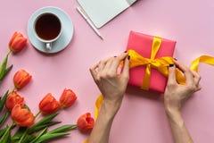 Mani femminili che tengono il contenitore di regalo rosso con il nastro giallo su fondo rosa fotografie stock