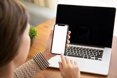 Mani femminili che tengono il telefono di tocco con lo schermo isolato sopra la tavola con il computer portatile nell'ufficio fotografia stock