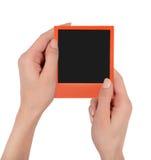 Mani femminili che tengono immagine arancio della polaroid immagini stock