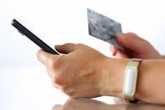 Mani femminili che tengono la carta di credito e che fanno usin online dell'acquisto Immagine Stock