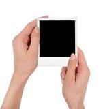 Mani femminili che tengono la foto della polaroid fotografia stock
