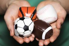 Mani femminili che tengono raccolta della palla di sport con calcio, rugby Fotografia Stock