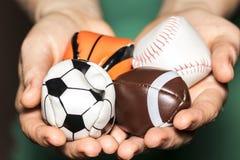 Mani femminili che tengono raccolta della palla di sport con calcio, rugby Immagine Stock