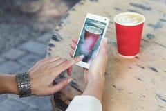 Mani femminili che tengono smartphone e che sparano caffè Immagini Stock Libere da Diritti