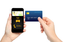 Mani femminili che tengono telefono con il taxi dell'interfaccia e la carta di credito o Fotografia Stock