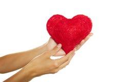 Mani femminili che tengono un cuore rosso Fotografia Stock