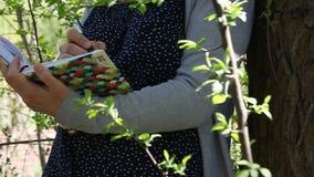 Mani femminili che tengono un diario di affari e che annotano qualcosa stock footage