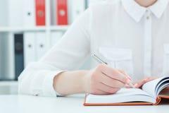 Mani femminili che tengono un primo piano d'argento della penna donna di affari che fa le note nel luogo di lavoro dell'ufficio Fotografia Stock
