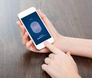 Mani femminili che tengono un telefono e che impostano il codice di PIN del dito fotografia stock