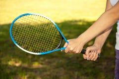 Mani femminili che tengono una racchetta di tennis Fotografia Stock