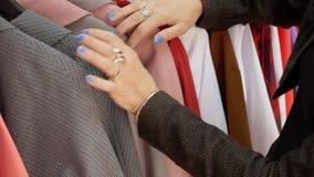 Mani femminili che toccano i vestiti sul gancio mentre comperando nel deposito di modo Donna che sceglie i vestiti di modo in sal stock footage