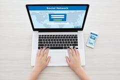 Mani femminili in computer portatile e telefono con la rete sociale sullo scre Immagini Stock