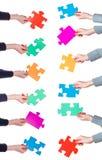 Mani femminili con differenti pezzi di puzzle Immagine Stock