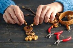 Mani femminili con fabbricazione colorata della collana delle perle Fotografie Stock