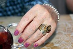 Mani femminili con gioielli sulle dita e sulla fine del braccialetto su immagine stock