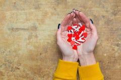 Mani femminili con i cuori rossi su una tavola di legno Immagine Stock Libera da Diritti