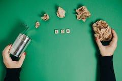 Mani femminili con il barattolo di alluminio e la carta sgualcita su un BAC verde Immagine Stock Libera da Diritti