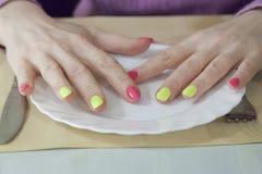 Mani femminili con il bello manicure su un piatto bianco Fotografia Stock