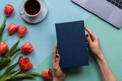 Mani femminili con il libro su fondo blu Fondo con caffè, il computer portatile ed i fiori fotografie stock libere da diritti