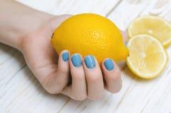 Mani femminili con il limone blu-chiaro della tenuta di arte del chiodo Fotografie Stock Libere da Diritti