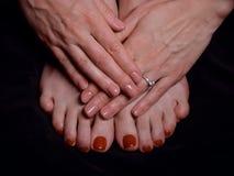 Mani femminili con il manicure e piedi con il pedicure Fotografia Stock