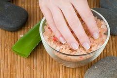 Mani femminili con il manicure francese ed il sale del mare Fotografia Stock