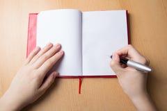 Mani femminili con la penna ed il taccuino Fotografie Stock