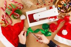 Mani femminili con le forbici che tagliano nastro rosso Natale diy Fotografie Stock