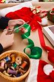 Mani femminili con le forbici che tagliano nastro verde Natale diy Fotografia Stock
