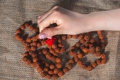 Mani femminili con le perle su tela da imballaggio Fotografia Stock Libera da Diritti