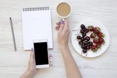 Mani femminili con lo smartphone, il latte, il taccuino, le fragole e le ciliege su fondo di legno bianco, vista superiore Dispos Fotografia Stock