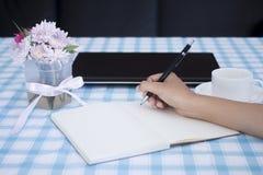 Mani femminili con scrittura della matita sul taccuino con il computer portatile Fotografia Stock Libera da Diritti