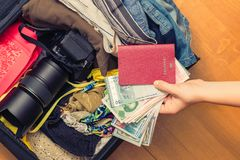Mani femminili con soldi asiatici ed il passaporto straniero Valigia con le cose sul pavimento concetto di corsa immagini stock