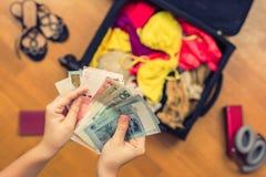 Mani femminili con soldi asiatici ed il passaporto straniero Valigia con le cose sul pavimento concetto di corsa fotografia stock libera da diritti