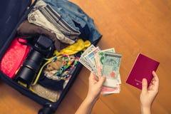 Mani femminili con soldi asiatici ed il passaporto straniero Valigia con le cose sul pavimento concetto di corsa fotografia stock
