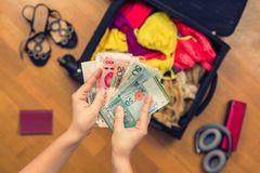 Mani femminili con soldi asiatici ed il passaporto straniero Valigia con le cose sul pavimento concetto di corsa immagini stock libere da diritti
