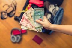 Mani femminili con soldi asiatici ed il passaporto straniero Valigia con le cose sul pavimento concetto di corsa immagine stock