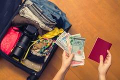 Mani femminili con soldi asiatici ed il passaporto straniero Valigia con le cose sul pavimento concetto di corsa fotografie stock
