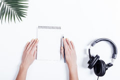 Mani femminili con un taccuino e una matita, cuffie e pianta sopra Fotografie Stock