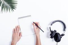 Mani femminili con un taccuino e una matita, cuffie e pianta sopra Immagini Stock